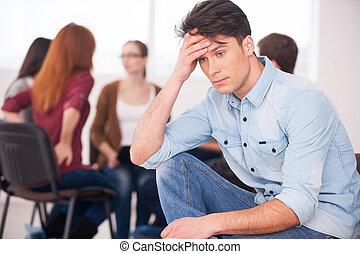 voelende pijn, en, depression., terneergeslagen, jonge man, zittende , op, de, stoel, en, het houden kop, in, hand, terwijl, anderen, mensen, het communiceren, op achtergrond