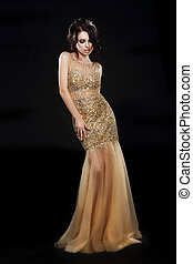 Vogue. Beautiful Fashion Model In Golden-Yellow Dress over Black