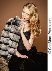 Elegant woman with beautiful blonde hair posing in furs. Luxury, rich lifestyle. Fashion photo.