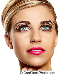 beautiful young blond woman face closeup wearing vogue long lashes and bright pink lipstick - naturally beautiful skin texture