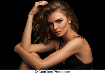 Vogue style close-up portrait of beautiful woman with long curly blond hair on black background