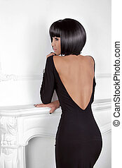 Vogue Style. Fashion Beauty Woman in sexy dress showing back. Brunette Lady with Black Short Hair Styling posing behind modern wall.