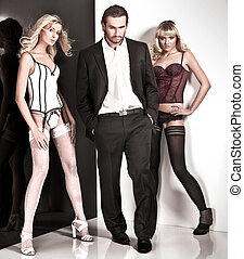 Vogue style studio shot of an handsome man and 2 women