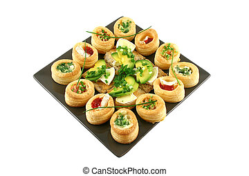 Assorted vol au vonts and avocado and camembert bites on a platter.