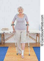vol lengte portret, van, een, het glimlachen, oude vrouw, met, krukken, staand, in het ziekenhuis, gym