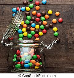 volcado, tarro de cristal, lleno, de, colorido, dulces
