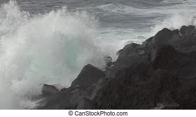 Volcanic coastline and waves breaking, super slow motion