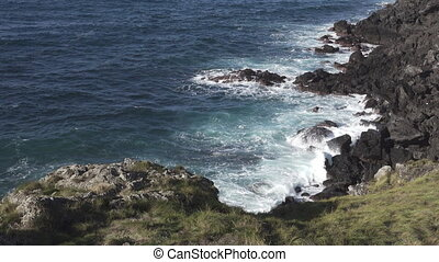 Volcanic coastline, waves breaking - Top view of volcanic...