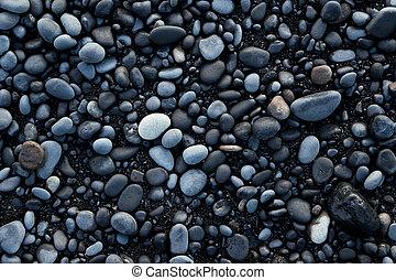 Volcanic rock on black sand beach.
