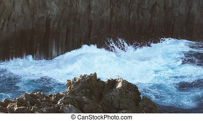 Volcanic vertical cliff and waves breaking - Vertical cliff...