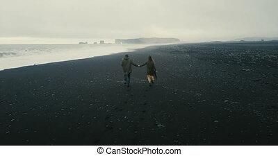 volcanique, aérien, romantique coupler, iceland., jeune, dos, courant, noir, sea., date, plage, vue