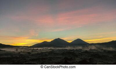 sunrise in kintamani. volcano Batur Bali Indonesiai. caldera view. unesco. Fast clouds moving. Timelapse hyperlapse 4K video. black lava. vulcano Abang Agung