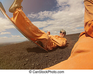 Volcano boarding activity man in orange costume Nicaragua
