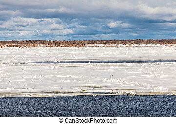 Volga river in Russia near the Nizhniy Novgorod city. The hummocks and floes on the winter river. The spring landscape of the sunny day with the snow, ice and thawed patches