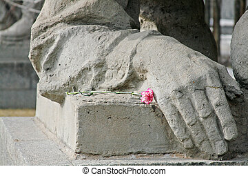 White-pink carnation lies on a pedestal next to the element of the monument of the Second World War n the Mamaev Kurgan in Volgograd