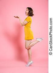 volles längenporträt, von, verspielt, attraktive, frau, in, gelbes kleid, stehen bein, ausstellung, leerer , handfläche