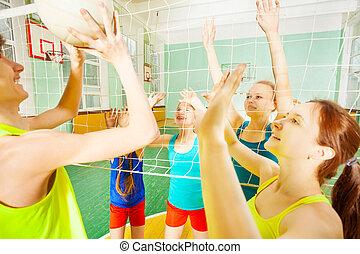 Volleyball game between teenage teams in gymnasium