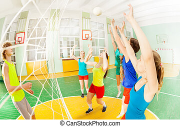 Volleyball game with group of teens in sports hall