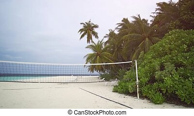 Volleyball Net and Palms in a Breeze in the Maldives -...