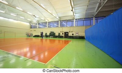 Volleyball net inside lighted school gym hall with...