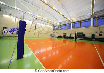 Volleyball net inside lighted school gym hall with green-...