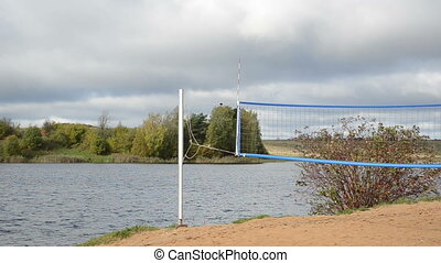volleyball net lake - volleyball net on lake shore in...