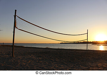 Volleyball net on beach at sunset