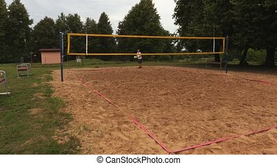 Volleyball player serves across the net