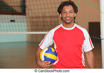 Volleyball player stood with ball under arm