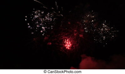 Volleys of celebratory fireworks in the night sky. Slow motion