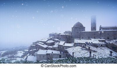 Volterra village during a snowfall in winter. Tuscany, Italy