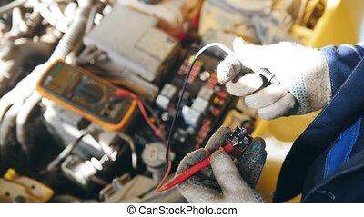 Voltmeter in the car - automotive electrician checks electro...