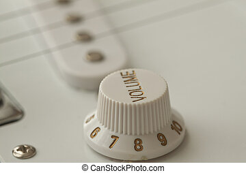 Volume knob near the strings of an electric guitar
