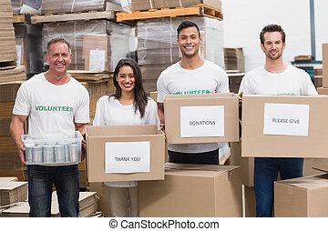 voluntários, sorrindo, câmera, segurando, doações, caixas
