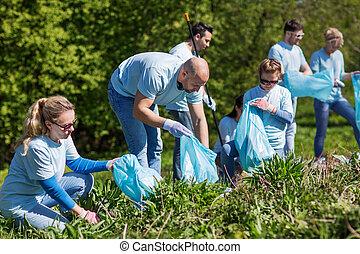 voluntarios, con, basura empaqueta, limpieza, parque, área