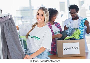 voluntarios, poniendo, alegre, carril de las ropas