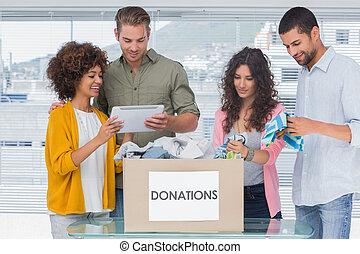 voluntarios, utilizar, tableta, y, sacar, ropa, de, un, caja...
