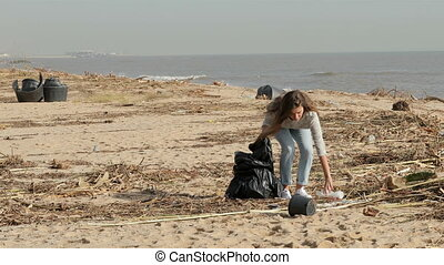 Full body of a volunteer picking up litter cleaning a dirty beach after storm