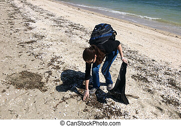 Volunteer collecting garbage on beach. Single-use,...