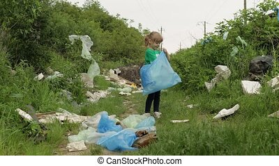 Volunteer child girl kid in green t-shirt tidying up rubbish in park, cleaning up dirty forest from plastic bags, bottles. Collect trash. Recycle. Reduce environment cellophane pollution. Save ecology