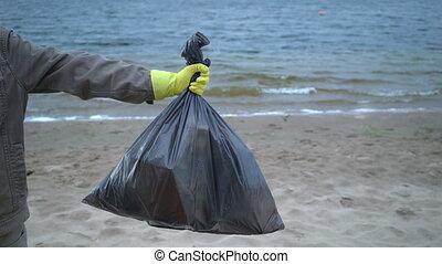 volunteer hands holding garbage bag on beach.