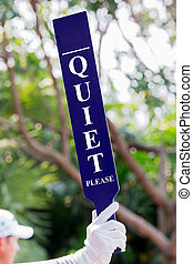 Quiet sign on the tee - volunteer holds up Quiet sign on the...