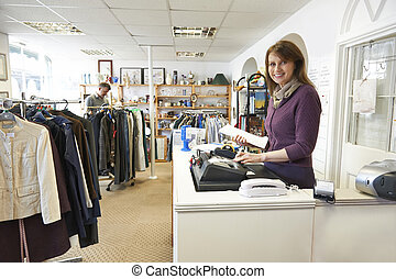 Volunteer In Charity Shop With Customer