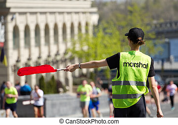Volunteer Marshal shows the direction of runners - Volunteer...