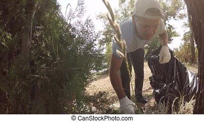 Volunteer removes debris in the forest, slow motion