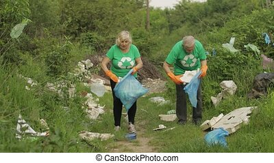 Volunteer team cleaning up dirty park of forest from plastic bags, bottles. Collect trash. Activist adult old grandparents caring about environment. Recycle. Reduce cellophane pollution. Save ecology