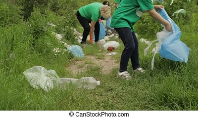 Volunteer team cleaning up dirty park from plastic bags, bottles. Collect trash. Activist child girl and adult grandparents caring about environment. Recycle. Reduce cellophane pollution. Save ecology