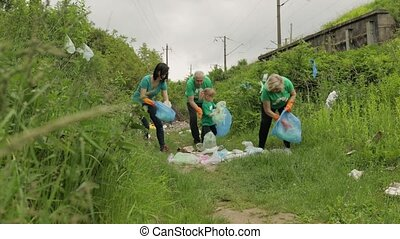 Volunteer team in T-shirts cleaning up dirty park from plastic bags, bottles. Collect trash. Activist child girl and adults caring about environment. Recycle. Reduce cellophane pollution. Save ecology