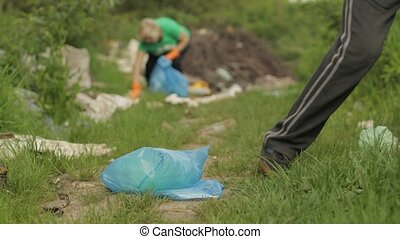 Close up voluteers activists in green t-shirt, gloves tidying up bags, bottles rubbish in forest park. Save environment stop plastic cellophane pollution. Recycle ecology garbage nature altruism
