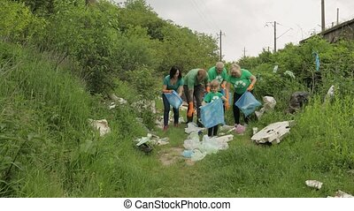 Volunteer team in T-shirts cleaning up park from plastic bags, bottles. Collect trash. Activist child girl and adults caring about environment. Recycle. Reduce trash cellophane pollution. Save ecology